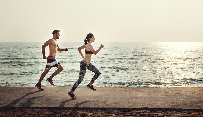 couple jogging by the beach