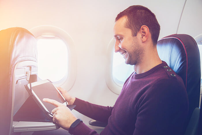 Young man using his tablet on a plane