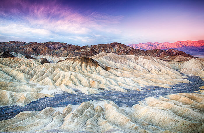 sun rises over Zabriskie Point in Death Valley